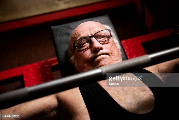 Senior man lifting weights in gym