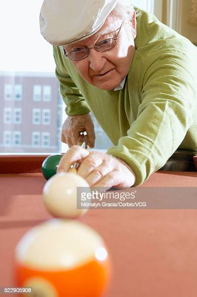 senior man lining up billiard shot - old men playing pool stock pictures, royalty-free photos & images
