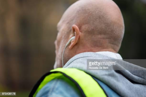 Senior woman Kopfhörer auf Bürgersteig anhören