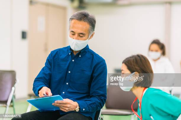 senior man listening to explanation for filling in medical record forms for vaccination procedure  in vaccination center - vaccination center stock pictures, royalty-free photos & images