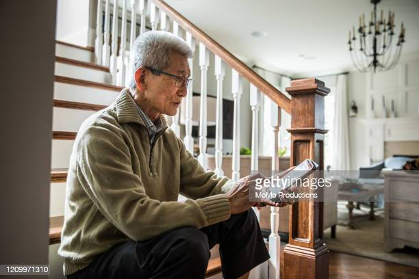 senior man listening to music on laptop wearing headphones - east asian ethnicity stock pictures, royalty-free photos & images