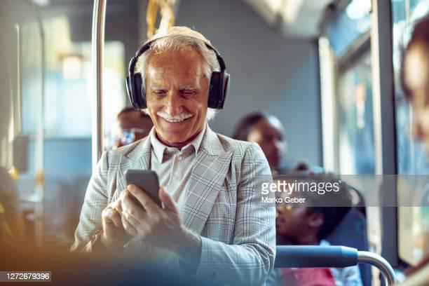 senior man listening to music while riding in a bus - verkehrswesen stock-fotos und bilder