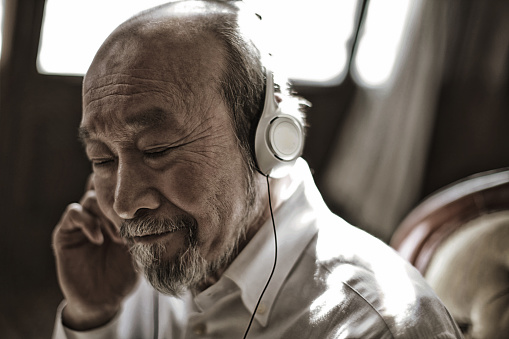 Senior man listening to music with closed eyes - gettyimageskorea