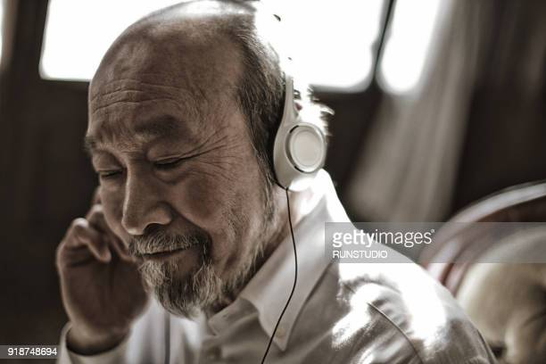 senior man listening to music with closed eyes - japanese old man stock pictures, royalty-free photos & images