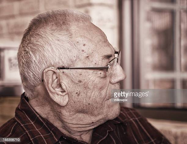 senior man listening with hearing aid - wart stock photos and pictures