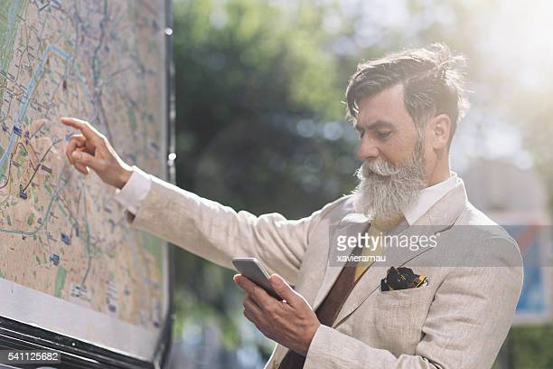 Senior man looking a Paris city map