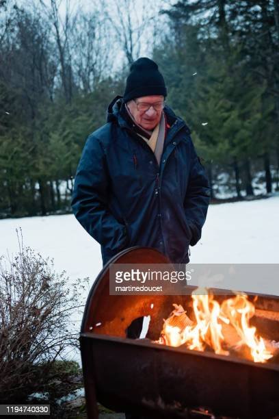 "senior man looking at a fire outdoors in winter - ""martine doucet"" or martinedoucet stock pictures, royalty-free photos & images"
