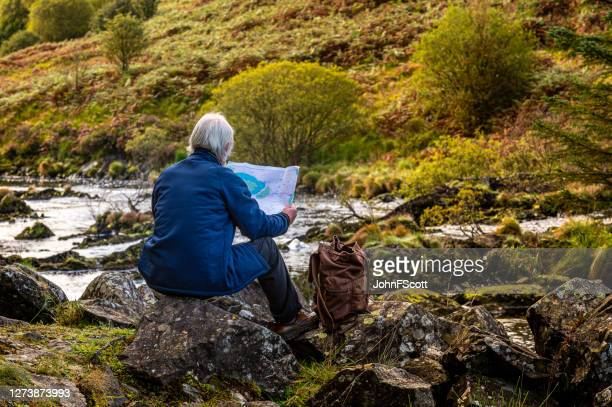 senior man looking at a map while sitting on a rock beside a scottish river in rural south west scotland. - johnfscott stock pictures, royalty-free photos & images