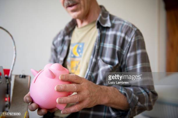 senior man looking at his 3d-printed piggy bank - financiën en economie stockfoto's en -beelden