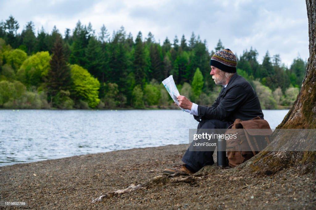 Senior man looking at his map : Stock Photo
