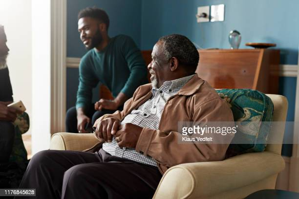 senior man looking at male friends talking at home - black jacket stock pictures, royalty-free photos & images