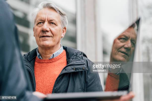 senior man looking at man holding laptop outdoors - successor stock pictures, royalty-free photos & images