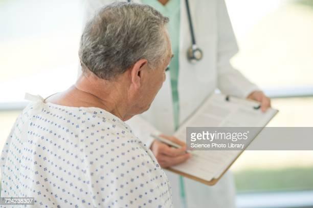 Senior man looking at medical notes in hospital
