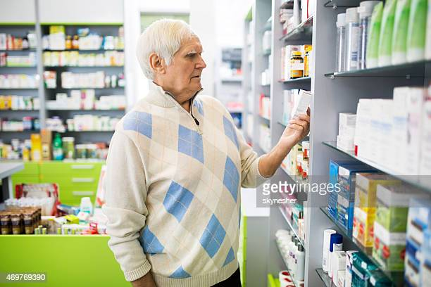 Senior man looking at medicine in a pharmacy.