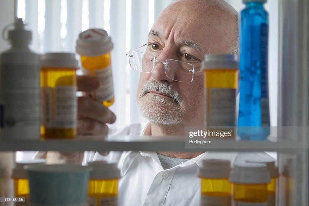 Senior man looking at prescription drugs : Stock Photo