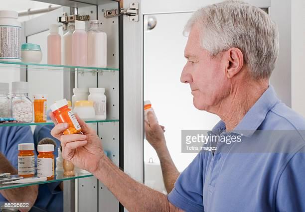 senior man looking at prescription - armoire de toilette photos et images de collection