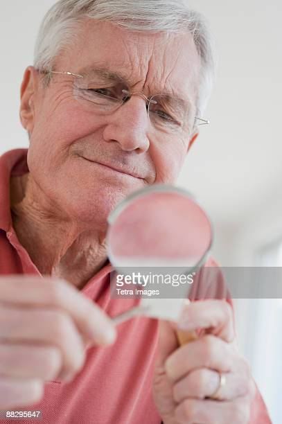 Senior man looking at stamp collection