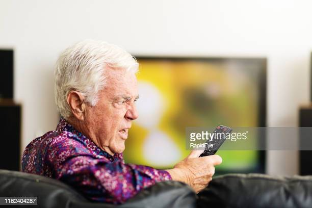 senior man looking at tv remote control, confused and irritated - ineptitude stock pictures, royalty-free photos & images