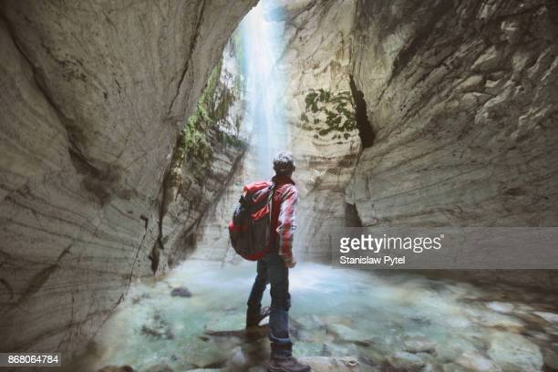 Senior man looking at waterfall inside of marble cave
