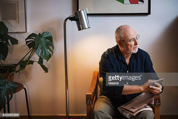 Senior man looking away while holding smart phone at home