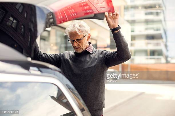 Senior man looking into car trunk while standing in city