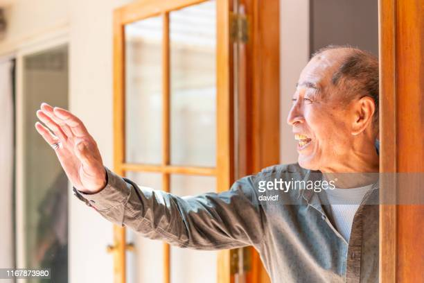 senior man looking out a doorway - waving stock pictures, royalty-free photos & images