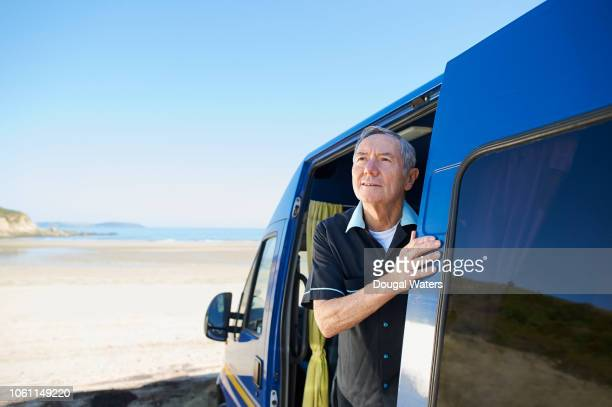 senior man looking out from camper van beside beach. - dougal waters stock pictures, royalty-free photos & images