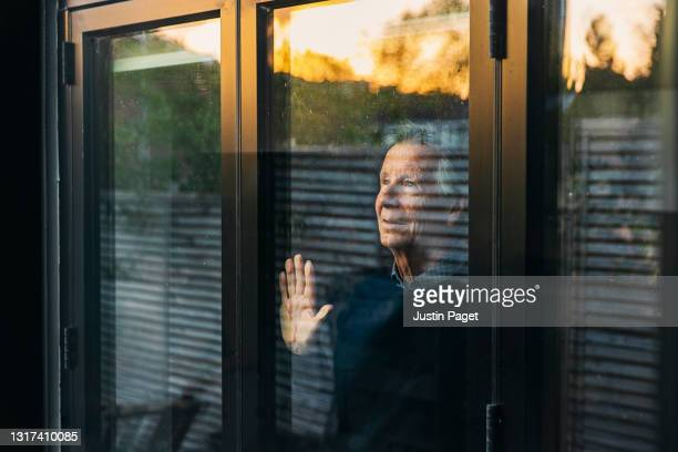 senior man looking out of his window at sunset - one senior man only stock pictures, royalty-free photos & images