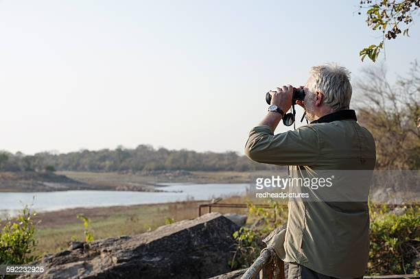 Senior man looking out through binoculars at river, Kafue National Park, Zambia