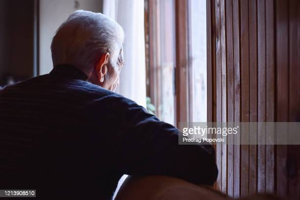 senior man looking outside from home window - einzelner senior stock-fotos und bilder