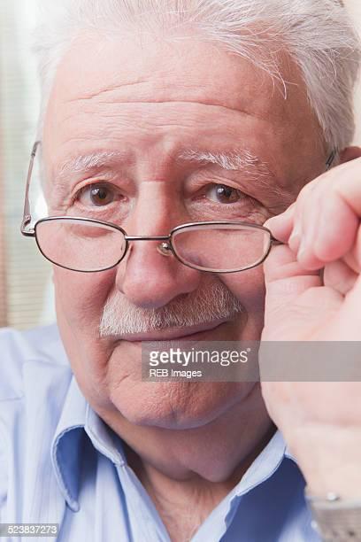 Senior man looking over glasses