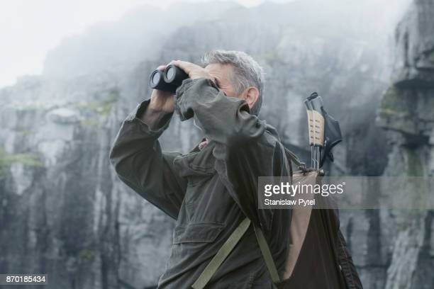 Senior man looking through binocular in mountains