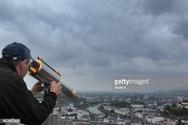 Senior man looking through binoculars of the city of Salzburg.