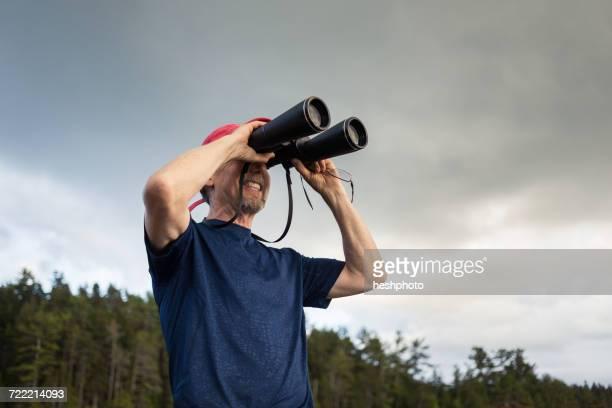 senior man looking through binoculars toward coast of maine, usa - heshphoto stock pictures, royalty-free photos & images