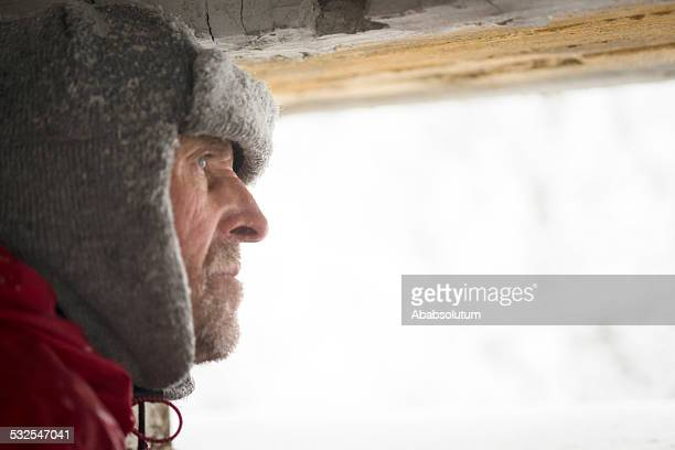 Senior Man Looking  through Great War's Bunker Porthole , Snowing, Europe