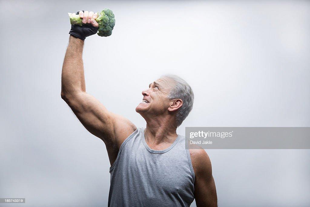 Senior man looking up and lifting broccoli : Stock Photo