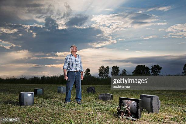 Senior man looking up on a field surrounded by televisions