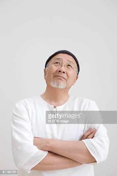 senior man looking upward with arms folded, portrait, close-up - 60代 ストックフォトと画像