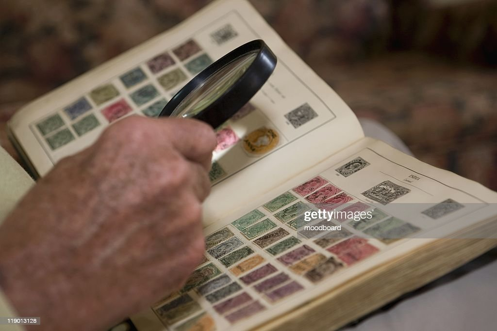 Senior man looks at stamp collection with magnifying glass : Stock Photo