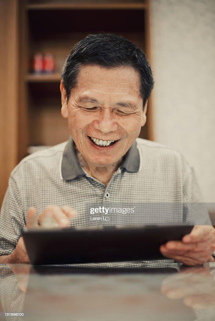 Senior man looks at tablet happily : Bildbanksbilder
