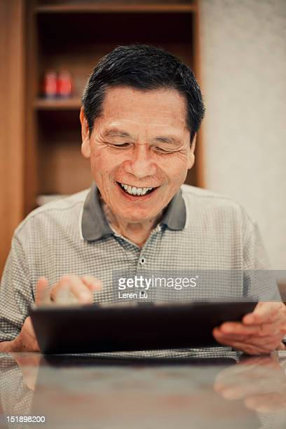 Senior man looks at tablet happily