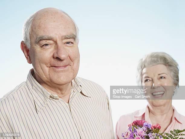 Senior man looks pleased that she likes the flowers