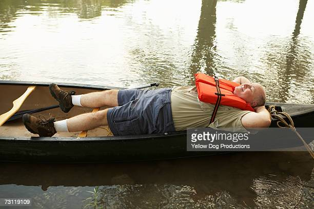 Senior man lying down in canoe, elevated view