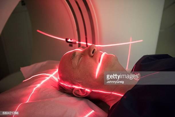 Senior man lying down receiving medical scan