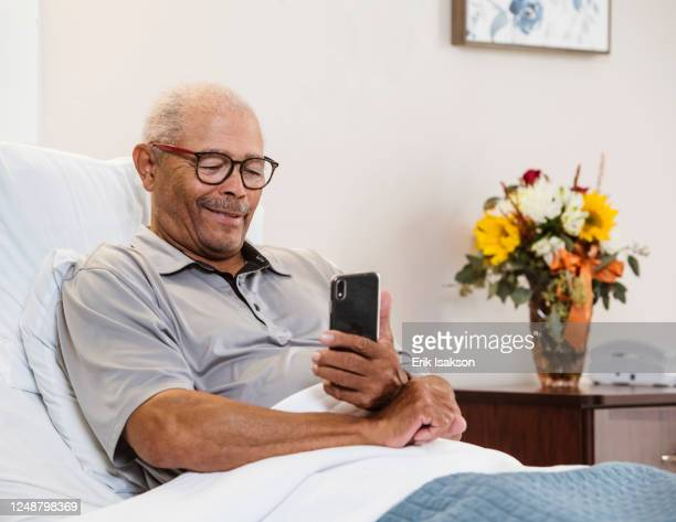 senior man lying in bed and using smart phone - leaning disability stock pictures, royalty-free photos & images