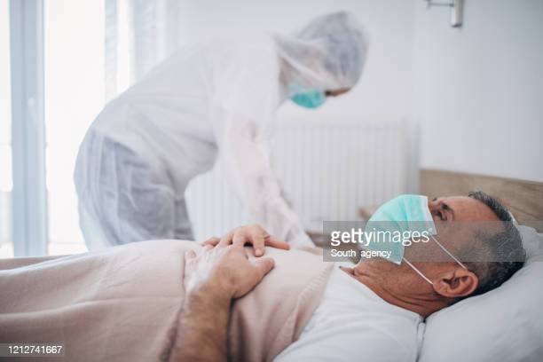 senior man lying in hospital bed because of coronavirus infection - infectious disease stock pictures, royalty-free photos & images