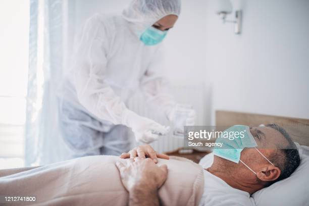 senior man lying in hospital bed because of coronavirus infection - medical condition stock pictures, royalty-free photos & images