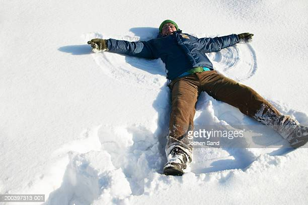senior man lying in snow making snow angel, smiling - snow angel stock photos and pictures