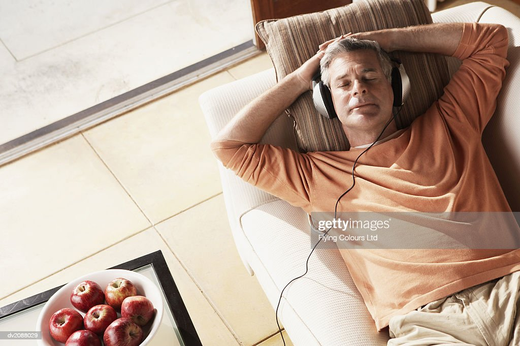 Senior Man Lying on a Sofa Listening to Music on Headphones : Stock Photo