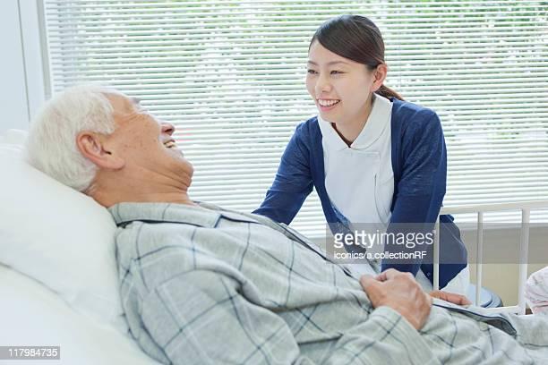 Senior man lying on bed talking to nurse, Kanagawa Prefecture, Honshu, Japan
